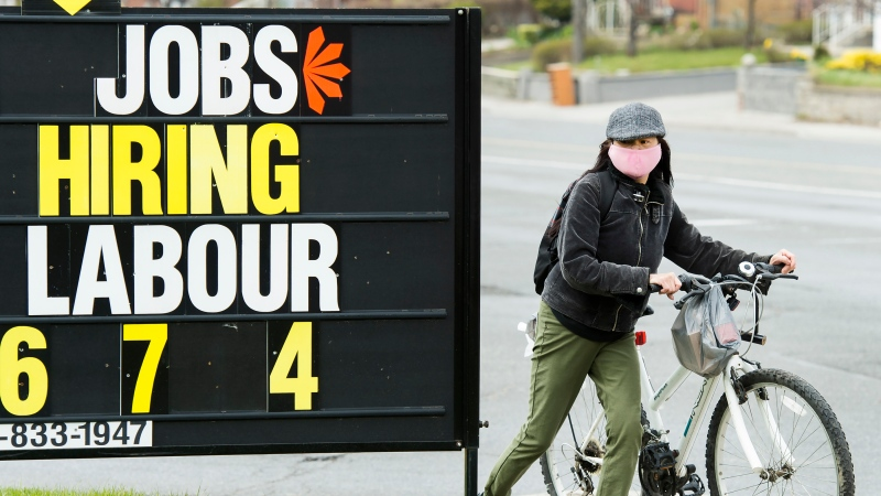 A woman checks out a jobs advertisement sign during the COVID-19 pandemic in Toronto on Wednesday, April 29, 2020. Statistics Canada will report this morning how the country's labour market performed in July as more parts of the economy were allowed to reopen. THE CANADIAN PRESS/Nathan Denette