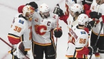 Calgary Flames players celebrate the win over the Winnipeg Jets during third period NHL qualifying round game action in Edmonton, on Thursday August 6, 2020. THE CANADIAN PRESS/Jason Franson