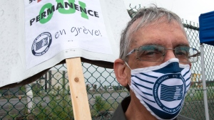 A striking Port of Montreal worker holds a sign as workers begin a four-day walkout, Monday, July 27, 2020 in Montreal. The union representing longshoremen at the Port of Montreal says it will launch a strike without an end date starting Monday. THE CANADIAN PRESS/Ryan Remiorz