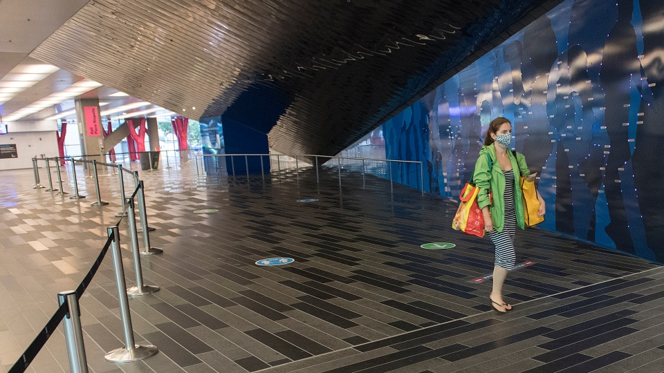 A woman wears a face mask as she walks through the Palais des congres in Montreal, Sunday, August 2, 2020, as the COVID-19 pandemic continues in Canada and around the world. The Quebec government has made the wearing of masks and face coverings mandatory in all public spaces as of July 18 and will increase the number of indoor and outdoor group gatherings to 250 people as of August 3rd. THE CANADIAN PRESS/Graham Hughes