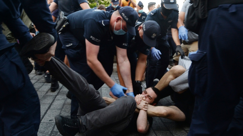 Police scuffle with pro-LGBT protesters angry at the arrest of an LGBT activist in Warsaw Poland on Friday, Aug. 7, 2020. The incident comes amid rising tensions in Poland between LGBT activists and a conservative government that is opposed to LGBT rights. (AP Photo/Czarek Sokolowski)