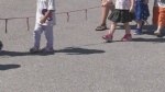 Young children hold a rope outside at daycare (CTV News)