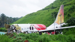 Officials stand on the debris of the Air India Express flight that skidded off a runway while landing in Kozhikode, Kerala state, India, Saturday, Aug. 8, 2020. (AP Photo/C.K.Thanseer)