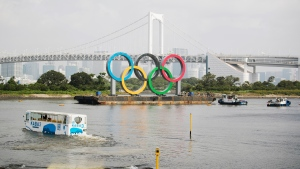 An amphibious bus wades through water for a test cruise as workers on tugboats prepare to move a symbol installed for the Olympic and Paralympic Games Tokyo 2020 on a barge away from its usual spot off the Odaiba Marine Park in Tokyo Aug. 6, 2020. (AP Photo/Hiro Komae)