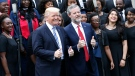 In this May 13, 2017 file photo, U.S. President Donald Trump poses with Liberty University president, Jerry Falwell Jr., center right, in front of a choir during of commencement ceremonies at the school in Lynchburg, Va. (AP Photo/Steve Helber, File)