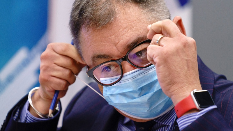 Dr. Horacio Arruda, Quebec's director of public health, removes his protective mask as he arrives at a news conference in Montreal, on Friday, Aug. 7, 2020. THE CANADIAN PRESS/Paul Chiasson