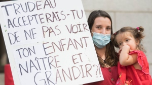A woman holds up a sign during a demonstration against government delays in family reunification certificates outside an immigration office in Montreal, Saturday, Aug. 8, 2020. The COVID-19 pandemic continues in Canada and around the world. THE CANADIAN PRESS/Graham Hughes