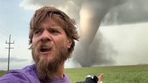 Storm chasers Aaron Jayjack stands in front of a massive tornado near Virden, Man. on Friday, Aug. 7, 2020. (Aaron Jayjack/ Twitter)