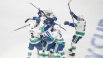 Vancouver Canucks players celebrate the win over the Minnesota Wild during overtime NHL qualifying round game action in Edmonton, on Friday August 7, 2020. THE CANADIAN PRESS/Jason Franson