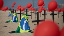 Crosses, red balloons and Brazilian nation flags are placed in the sand on Copacabana beach in a demonstration organized by Rio de Paz to honor the victims of COVID-19, as the country heads to a milestone of 100,000 new coronavirus related deaths, in Rio de Janeiro, Brazil, Saturday, Aug. 8, 2020. (AP Photo/Mario Lobao)