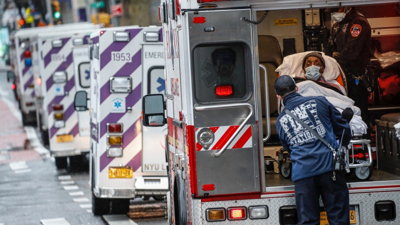 In this Monday, April 13, 2020, file photo, a patient arrives in an ambulance cared for by medical workers wearing personal protective equipment due to coronavirus concerns outside NYU Langone Medical Center in New York. AP Photo/John Minchillo, File)