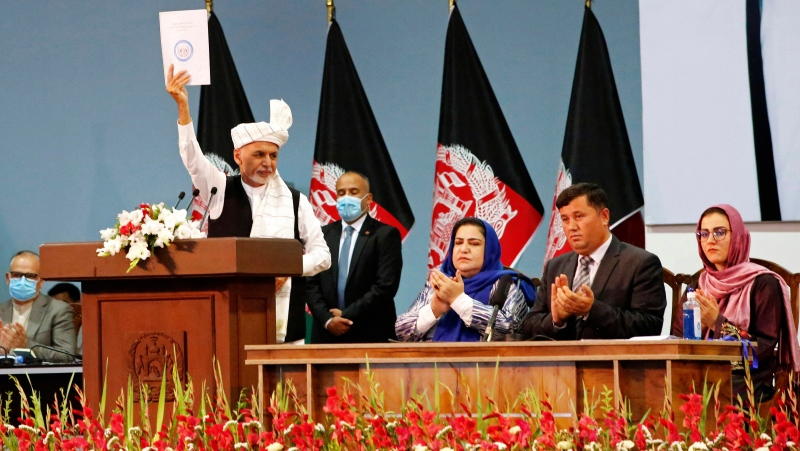 Afghan President Ashraf Ghani holds up the resolution on the last day of an Afghan Loya Jirga or traditional council, in Kabul, Afghanistan, Sunday, Aug. 9, 2020. (AP Photo)