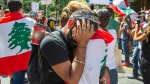 Guy Younnes is comforted by a friend as people take part in a protest demanding the resignation of the Lebanese government over their handling of the Beirut expolsion in front of the Lebanese consulate in Montreal, Friday, Aug. 7, 2020. THE CANADIAN PRESS/Ryan Remiorz
