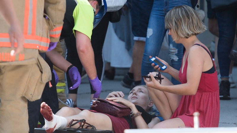 First responders attend to an injured woman after a jeep sped down a pedestrian zone on Sainte-Catherine Street in Montreal, Saturday, Aug. 8, 2020.THE CANADIAN PRESS/Graham Hughes
