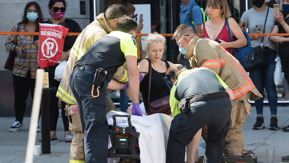 A woman is helped onto a stretcher by paramedics after a jeep sped down a pedestrianized zone on Sainte-Catherine Street in Montreal, Saturday, Aug. 8, 2020.THE CANADIAN PRESS/Graham Hughes