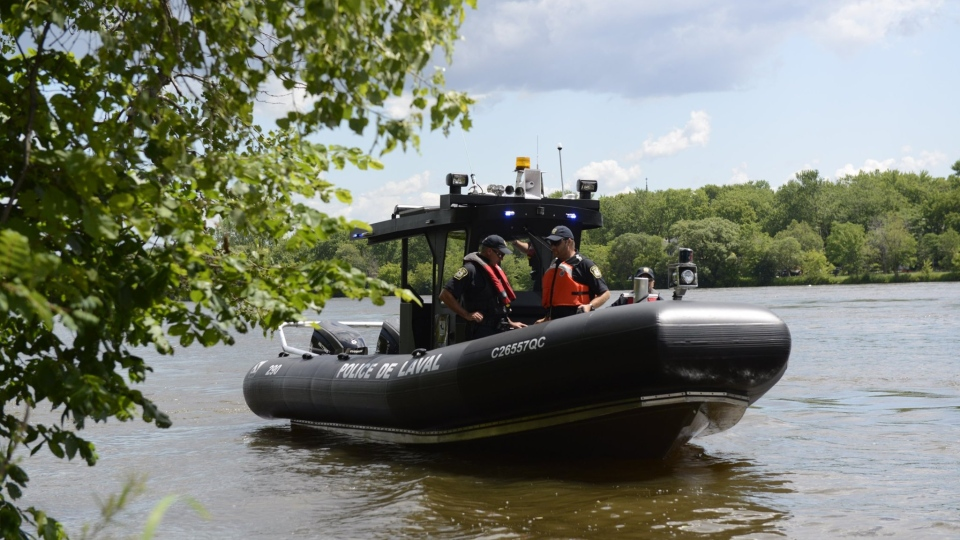 Laval police officers search the river