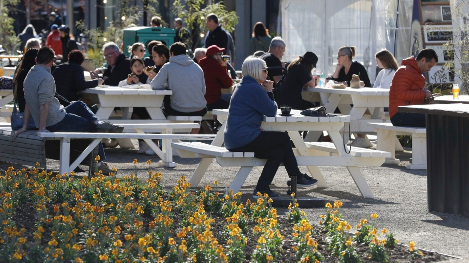 Customers enjoy lunch in the sunshine at the Riverside Market in Christchurch, New Zealand, Sunday, Aug. 9, 2020. (AP Photo/Mark Baker)