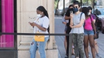 People wear face masks as they wait to enter a store in Montreal, Saturday, Aug. 8, 2020, as the COVID-19 pandemic continues in Canada and around the world. THE CANADIAN PRESS/Graham Hughes