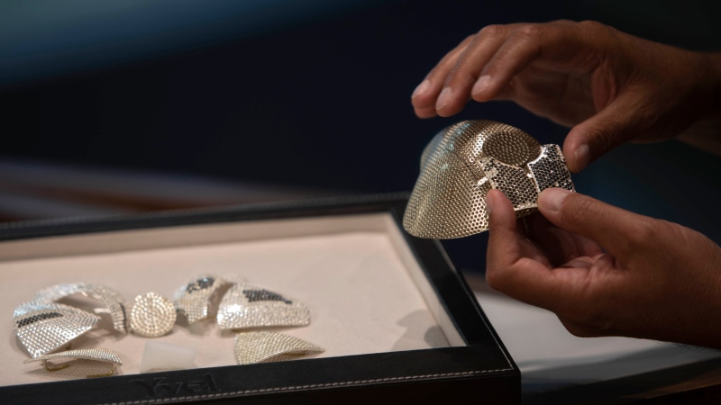 Isaac Levy, owner of Israeli jewelry company Yvel holds parts of a mask in Motza near Jerusalem, Sunday, Aug. 9, 2020. (AP Photo/Sebastian Scheiner)