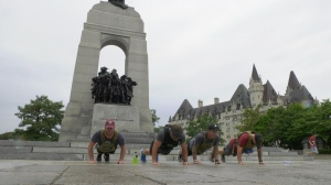 Dylan Pace and his Walk for the Wounded team do push-ups at the National War Memorial after completing the 175 kilometre walk from Petawawa. (Dave Charbonneau/CTV News Ottawa)