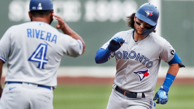 Toronto Blue Jays' Bo Bichette celebrates his solo home run with third base coach Luis Rivera (4) during the sixth inning of a baseball game against the Boston Red Sox, Sunday, Aug. 9, 2020, in Boston. (AP Photo/Michael Dwyer)