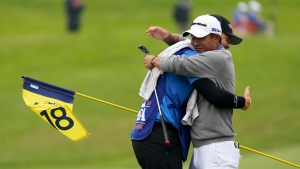 Collin Morikawa greets his caddie Jonathan Jakovac on the 18th hole after their final round of the PGA Championship golf tournament at TPC Harding Park Sunday, Aug. 9, 2020, in San Francisco. (AP Photo/Charlie Riedel)