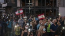 Demonstrators march past a damaged building holding candles and flashlights honoring the victims of the deadly explosion at Beirut port which devastated large parts of the capital, in Beirut, Lebanon, Sunday, Aug. 9, 2020. (AP Photo/Felipe Dana)