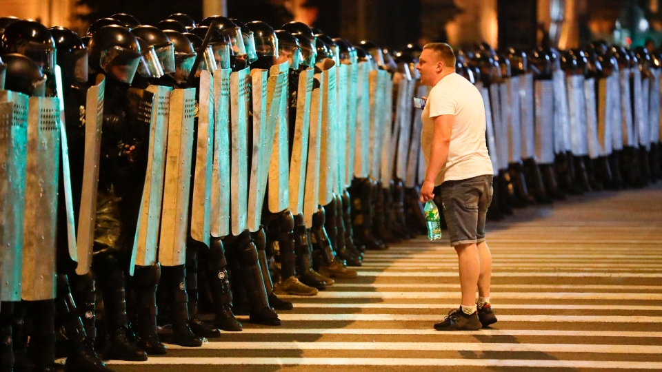 A protester speaks to police as they block the road during a rally after the Belarusian presidential election in Minsk, Belarus, Sunday, Aug. 9, 2020. (AP Photo/Sergei Grits)