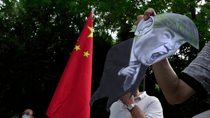 In this Aug. 8, 2020, file photo, pro-China supporters display a picture of U.S. President Donald Trump during a protest against the U.S. sanctions outside the U.S. Consulate in Hong Kong. (AP Photo/Vincent Yu, File)