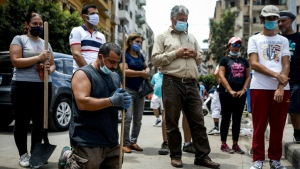 Volunteers and civil society members, mask-clad due to the COVID-19 pandemic, attend an outdoor Sunday mass held by a Maronite Christian priest in the Mar Mikhael neighbourhood of Lebanon's capital Beirut. (AFP)