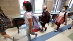 Wearing masks to prevent the spread of COVID19, elementary school students walk to class to begin their school day in Godley, Texas, Wednesday, Aug. 5, 2020. Three rural school districts in Johnson County were among the first in Texas to head back to school for in person classes for students. (LM Otero/AP)
