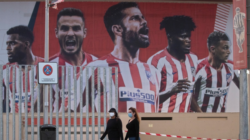 In this May 5, 2020 file photo, two women wearing face masks pass by a giant poster of Atletico Madrid soccer players at the Wanda Metropolitano stadium in Madrid, Spain. (AP Photo/Paul White, File)