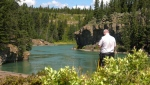 An RCMP member on the banks of the Bow River near the Seebe Dam during the search for a missing teen