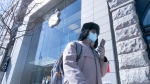 A man wearing a protective mask walks an Apple Store in downtown Montreal on Monday, March 16, 2020. Apple had closed their store world wide to help to curb the coronavirus from spreading. THE CANADIAN PRESS/Paul Chiasson