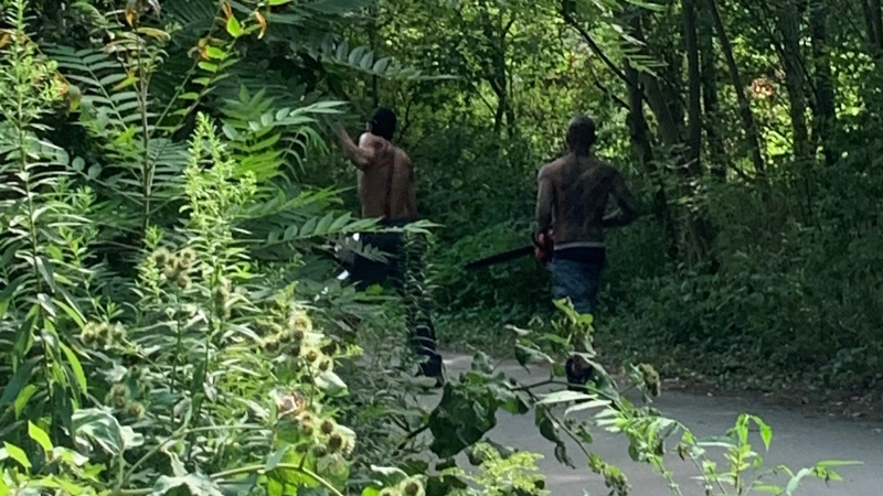 Men carrying chainsaws are seen near Cherry Beach on Aug. 9, 2020. (Anonymous)