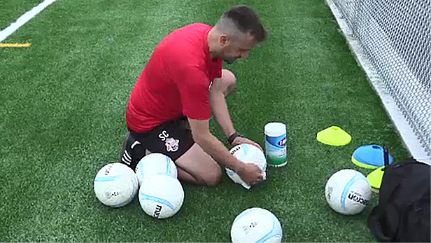 Sanir Cosovic, London TFC Academy coach, sanitizes soccer balls after practice in London, Ont. on Sunday, Aug 9, 2020. (Brent Lale / CTV News)