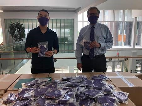 Student Jessie Brown, back left, Kevin Vuong founder of Take Care and Minister Monte McNaughton are shown with the new masks for Western students. (Jordyn Read / CTV London)