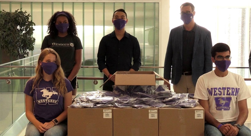 Student Jessie Brown, left, Kevin Vuong founder of Take Care and Minister Monte McNaughton are shown with the new masks for Western students. (Jordyn Read / CTV London)