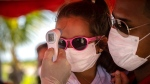 A little girl wearing a face mask amid the new coronavirus pandemic gets her temperature taken at a police checkpoint, at the entrance to the province of Havana, Cuba, Monday, Aug. 10, 2020. (AP Photo/Ramon Espinosa)