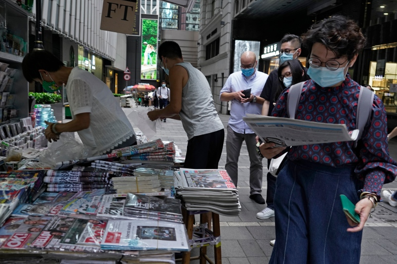 People queue up at a news stand to buy copies of Apple Daily at a downtown street in Hong Kong Tuesday, Aug. 11, 2020, as a show of support, a day after the arrest of its founder Jimmy Lai. Hong Kong authorities arrested media tycoon Jimmy Lai on Monday, broadening their enforcement of a new national security law and stoking fears of a crackdown on the semi-autonomous region's free press. (AP Photo/Vincent Yu)