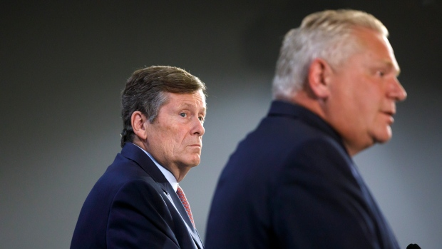 Toronto Mayor John Tory looks on at Ontario Premier Doug Ford as the two levels of government speak to media to announce additional funding for Toronto Police CCTV programs, at the Toronto Police College in Toronto, Friday, Aug. 23, 2019. THE CANADIAN PRESS/Cole Burston