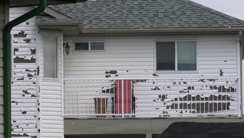 Shredded siding on a home in northeast Calgary after the community was peppered by massive hailstones during a June 13, 2020 storm