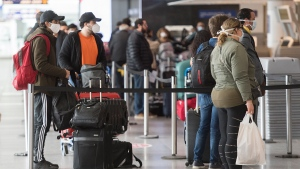 Passengers wear masks as they wait to check-in at Montreal-Pierre Elliott Trudeau International Airport, Saturday, May 16, 2020, as the COVID-19 pandemic continues in Canada and around the world. THE CANADIAN PRESS/Graham Hughes