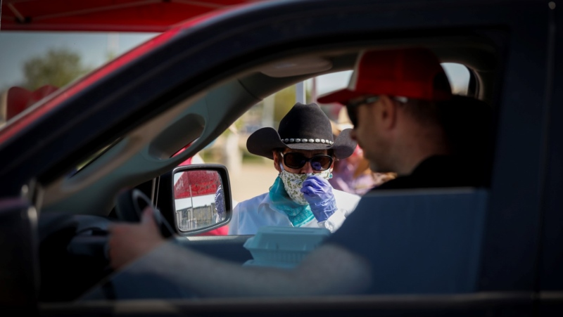 Calgary Stampede volunteer Jill Tynan speaks with a driver during a drive-thru pancake breakfast as people try to enjoy the Calgary Stampede even though it has been cancelled in Calgary, Saturday, July 4, 2020. THE CANADIAN PRESS/Jeff McIntosh
