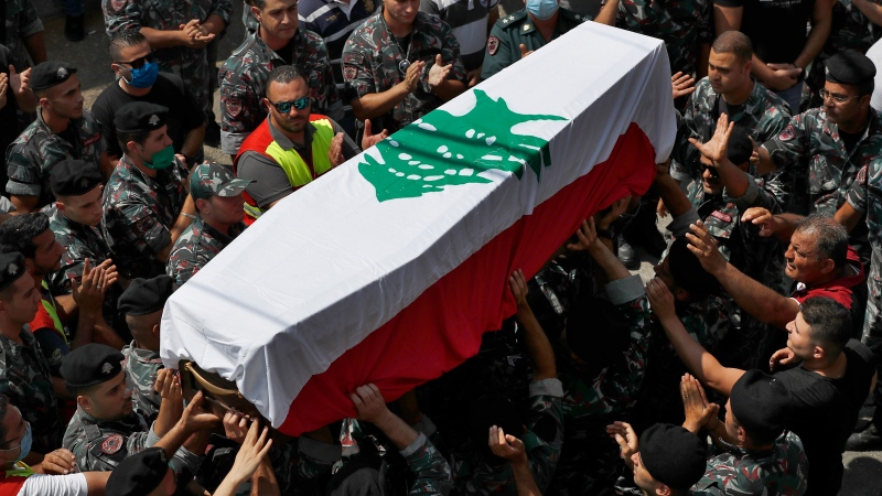 Firefighters carry the coffin of their comrade Rami Kaaki, one of ten firefighters who were killed during the last week's explosion that hit the seaport of Beirut, as friends and relatives applaud, during his funeral at the firefighter headquarters in Beirut, Lebanon, Tuesday, Aug. 11, 2020. (AP Photo/Hussein Malla)