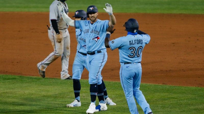 Toronto Blue Jays Travis Shaw celebrates his game-winning hit with Anthony Alford against Miami Marlins during extra innings of a baseball game, Tuesday, Aug. 11, 2020, in Buffalo, N.Y. (AP Photo/Jeffrey T. Barnes)