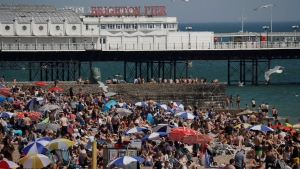 In this file photo dated Wednesday, June 24, 2020, large numbers of people relax on the beach in Brighton, England. (AP Photo/Matt Dunham, File)