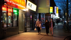 A passer-by carries take-out food in Toronto's Chinatown, on Saturday March 21, 2020. THE CANADIAN PRESS/Chris Young