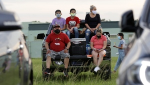 Yamil Carcamo, bottom left, sits with his family at a drive-in road rally to watch a telecast of the Miami Heat basketball team playing the Boston Celtics during the coronavirus pandemic, Tuesday, Aug. 4, 2020, in North Miami, Fla. (AP Photo/Lynne Sladky)