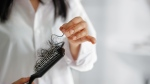 This stock image shows a woman's hair on her hairbrush. (ipopba / iStock)